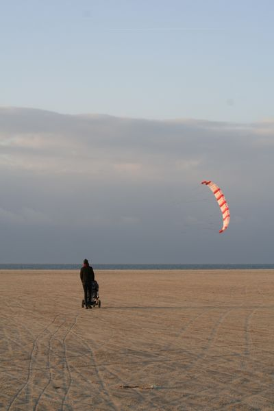 Mrs.B on the beach with a kite in the background